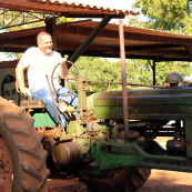 Photo: Kansas Wheat Commissioner Doug Keesling sits on an old John Deere tractor at a farm in Cuba.