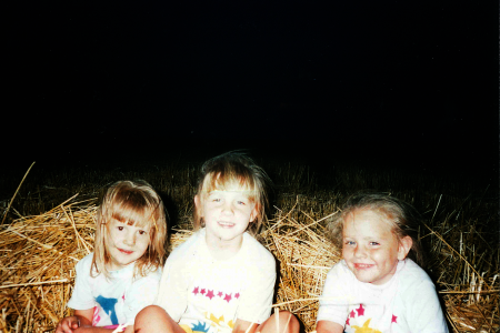Jordan and her cousins in a wheat field.